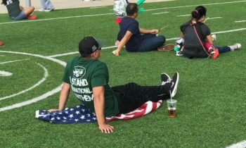 Idiot Jets Fan Caught Sitting On Flag While Wearing 'Stand For Anthem' Shirt