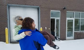 Doctor Opens Office And Carries Elderly Patient Through Snow-Filled Parking Lot